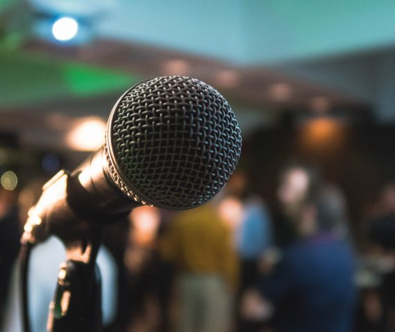 Close up of a microphone in the foreground with a group of people blurred int he background