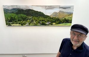 Photograph showing a painting of a landscape on a white gallery wall in the background, with a man wearing a cap, the artist, standing in the right foreground