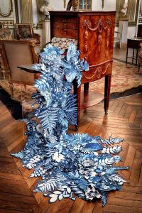 Photograph of an artwork located in a period museum setting, consisting of blue cyanotype botinic forms cascading from an antique wooden cabinet