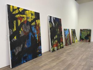 Photograph of large, colourful paintings propped up against the wall of a gallery