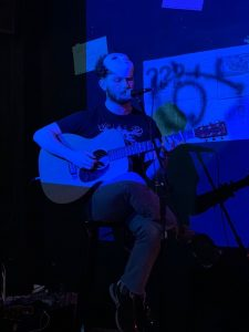 Photograph of a man playing a guitar while sitting on a stool, in a dark interior, lit by blue light