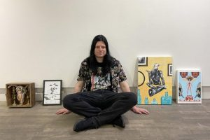 Photograph of artist sitting crosslegged on the floor of a gallery, surrounded by pieces of his art propped againt the wall.