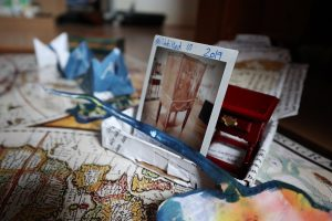 Photograph of artist's work in progress, consisting of small cyanotype pieces, and a polaroid picture of an antique cabinet propped up in a paper tray, all resting on a map
