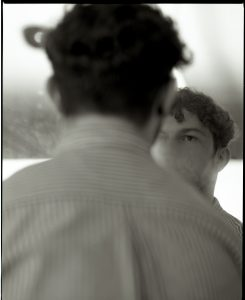 Black and white photograph of the back of the head and shoulders of a man, with his face reflected o=in a mirror on the right hand side