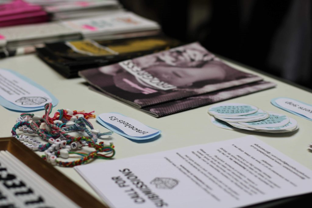 Woven bracelets, stickers, leaflets and zines on a table