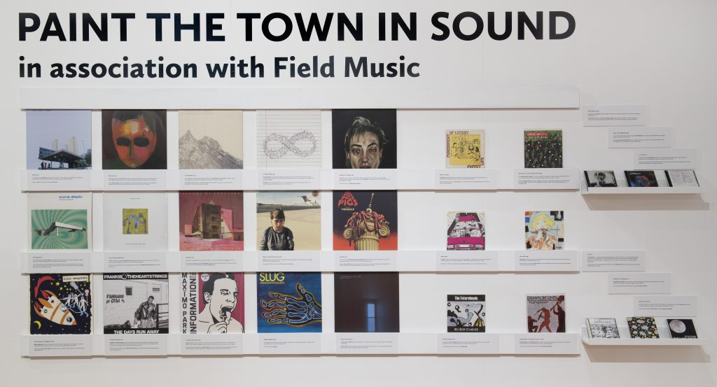 Display of album covers in a grid pattern on a white gallery wall, under the title label Paint The Town In Sound with Field Music