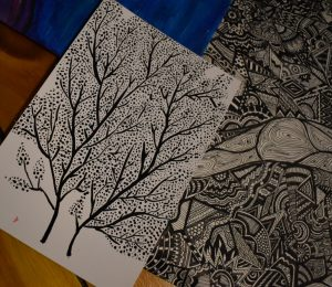 Abstracted, heavily patterned pen and ink drawings of trees laid out on a table
