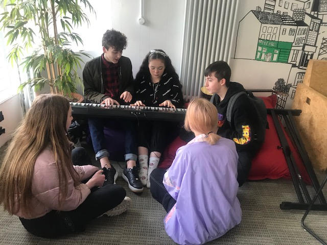 Group of young people clustered around, playing a keyboard