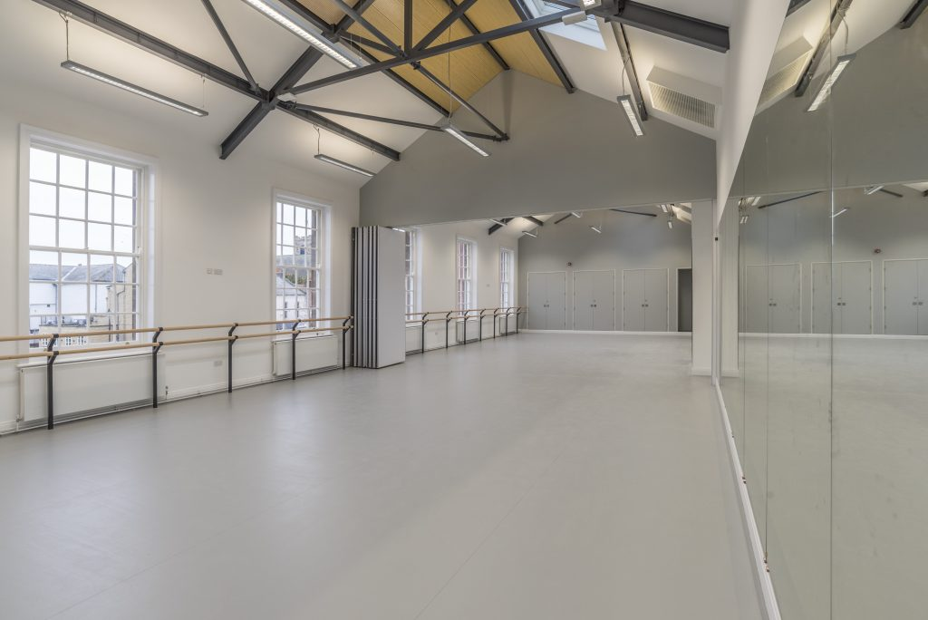 Image shows a dance studio space in The Fire Station, Sunderland. The studio is a long white-walled room with grey floor and a grey partition wall in the centre. The wall on the right hand side is lined with mirrors reflecting the empty room and the left hand wall is lined with large multi-paned windows with a wooden rail running along the wall from end to end. The ceiling is vaulted with strip white lights hanging from black beams.
